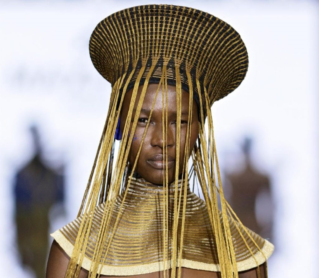 A model wearing a handcrafted Maxhosa Africa basket hat and neck piece