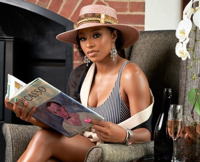 DJ Zinhle sitting down in a lounge and a holding a book