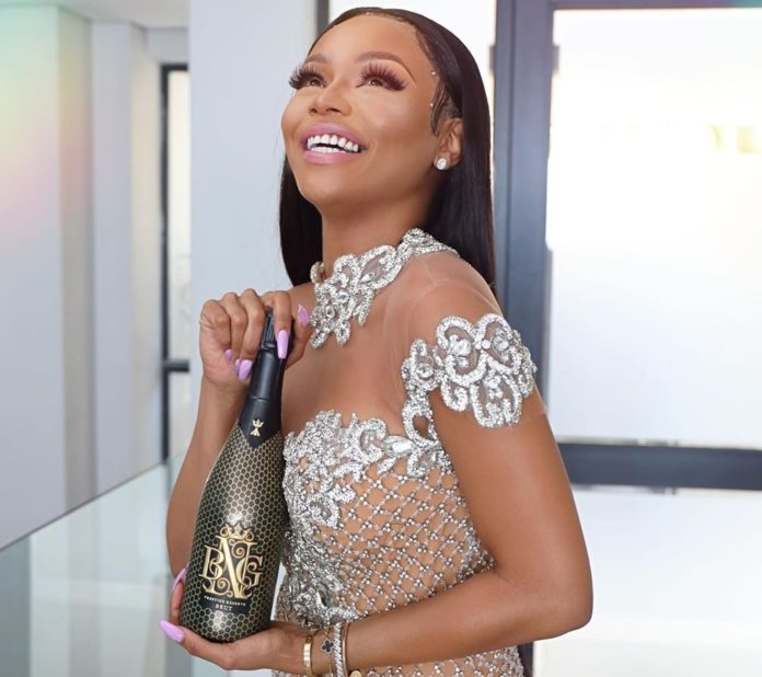 South African business woman Bonang Matheba holding a bottle of her new champaigne line, Prestige Reserve Brut