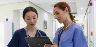 Two female nurses looking / reading a report on a tablet