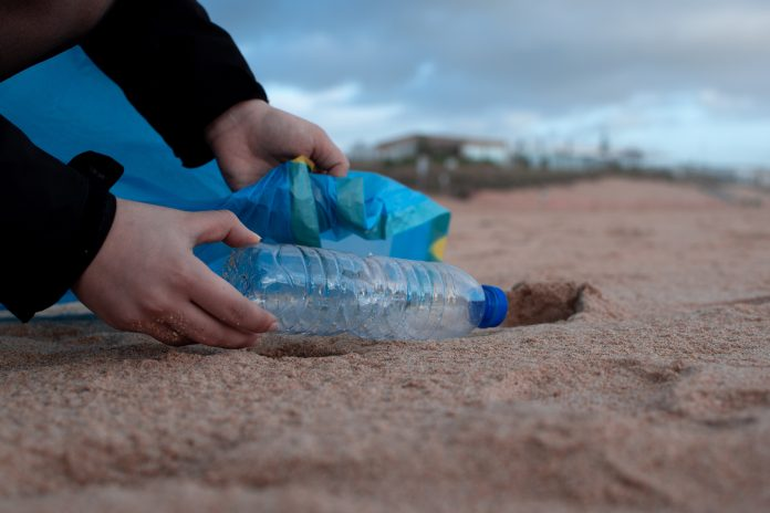 waste picker bends down to collect a discarded plastic bottle