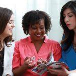 Three Avon female representatives looking at Avon's product catalog