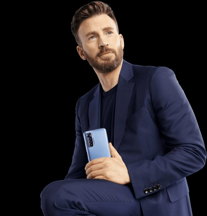 A mansitting on a chair poses for a picture holding Tecno Camon 17 Pro